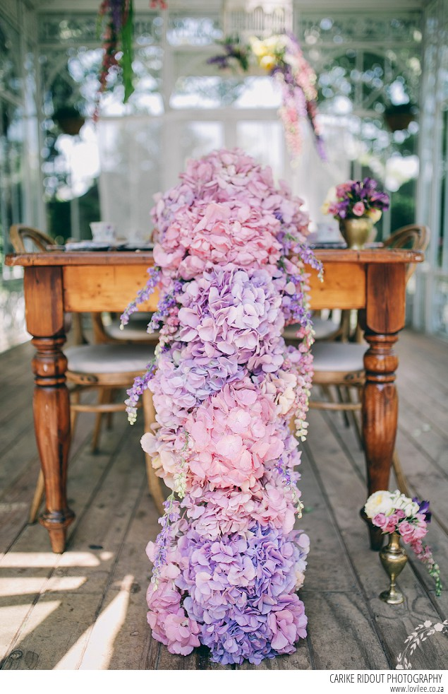 Bridal styled shoot with hydrangea table runner in a greenhouse